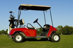 a red golf cart and golf clubs on a golf course
